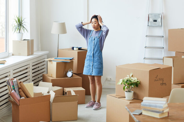 Frustrated Asian woman panicking while standing among cardboard boxes, cost-saving tips for moving